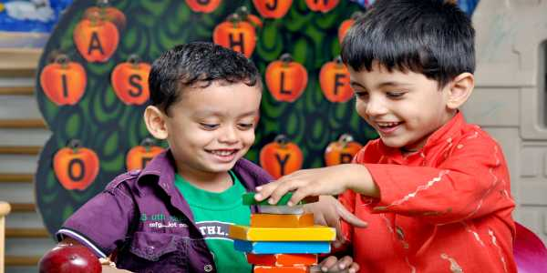Two Young kids Sitting on the table and playing with building blocks.