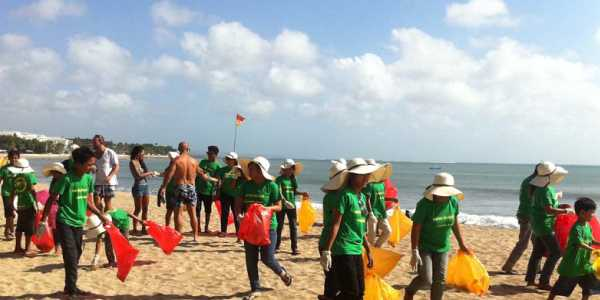 Group of Children standing on the sandy beach and doing some service related activity.