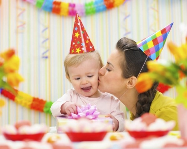 A Happy Mother Kissing Her Cute Smiling Child During Birthday Celebration.